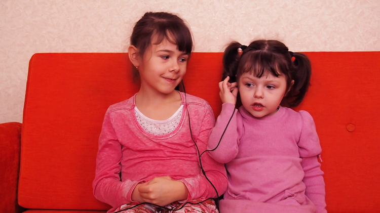 child sharing earphones